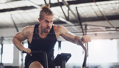 Buy stock photo Shot of a young man working out on an exercise bike in a gym
