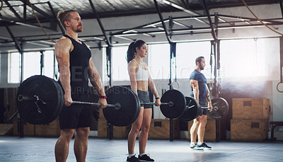 Buy stock photo Shot of a group of people exercising together with barbells in a gym