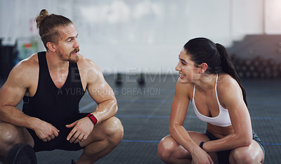 Buy stock photo Shot of two people taking a break while exercising in a gym