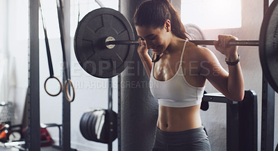 Buy stock photo Shot of a young woman exercising with a barbell in a gym