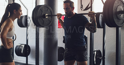 Buy stock photo Shot of a man exercising with a barbell with the help of a trainer in a gym