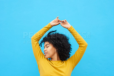 Buy stock photo Shot of a beautiful young woman looking content while posing against a blue background