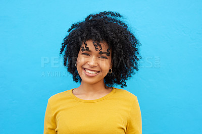 Buy stock photo Cropped shot of a young woman looking happy while posing against a blue wall