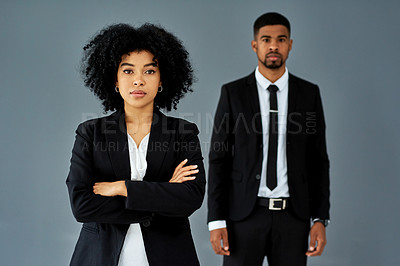 Buy stock photo Studio shot of a confident young businesswoman standing front of her colleague against a grey background