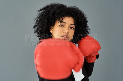 Buy stock photo Shot of young businesswoman wearing red boxing gloves against a grey studio background