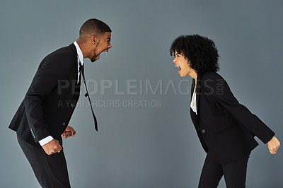 Buy stock photo Studio shot of a young businessman and businesswoman yelling at each other against a grey background