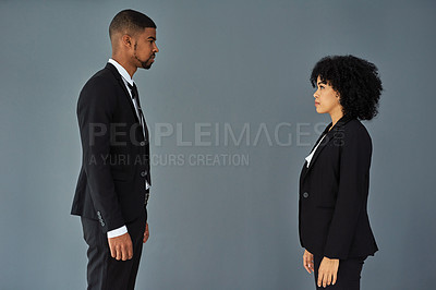 Buy stock photo Shot of young businessman and businesswoman standing face to face against a grey studio background