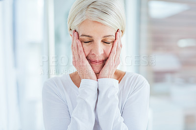 Buy stock photo Shot of a mature woman touching her face in a bathroom at home