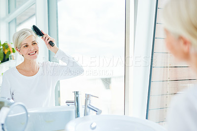 Buy stock photo Shot of a mature woman brushing her hair in a bathroom at home