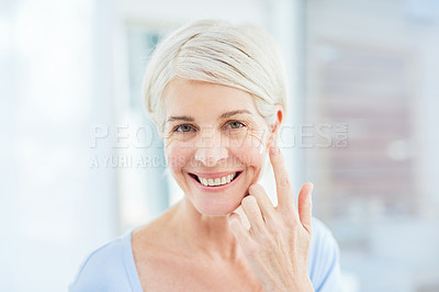 Buy stock photo Portrait of a mature woman applying moisturiser to her face in a bathroom at home
