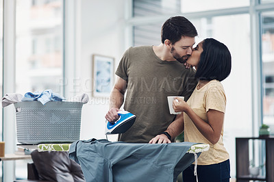 Buy stock photo Shot of an affectionate young couple ironing freshly washed laundry together at home