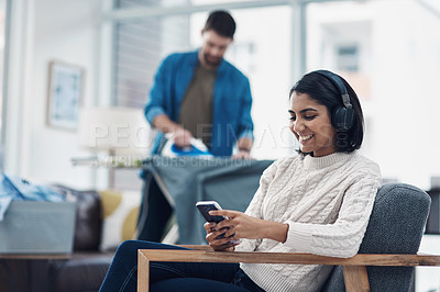 Buy stock photo Shot of a young woman using a smartphone and headphones while her husband irons clothing in the background