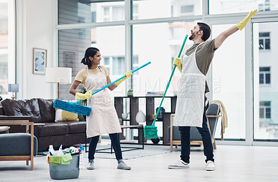Buy stock photo Shot of a happy young couple having fun while mopping the floor at home