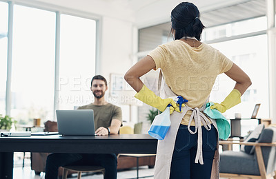 Buy stock photo Shot of a young woman cleaning the house while her husband uses a laptop