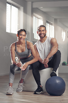 Buy stock photo Shot of two young athletes sitting together at the gym