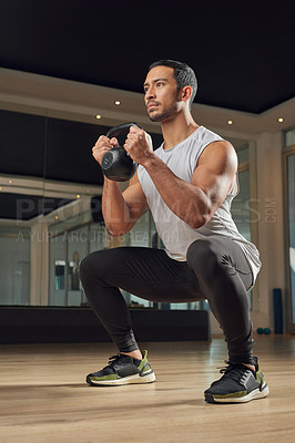 Buy stock photo Full length shot of a handsome young male athlete doing squats while holding a kettle bell in the gym