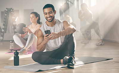 Buy stock photo Shot of a man using his cellphone while on a break at the gym