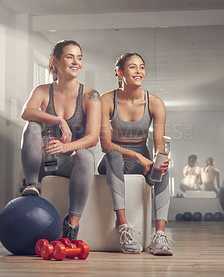Buy stock photo Shot of two young women looking happy while sitting together at the gym