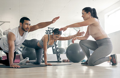 Buy stock photo Shot of two young athletes working out with their coach at the gym