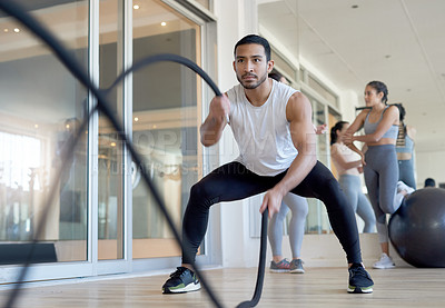 Buy stock photo Shot of a man using battle ropes while working out at the gym