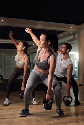 Buy stock photo Full length shot of three young athletes working out with kettle bells in the gym