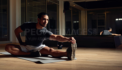 Buy stock photo Full length shot of a handsome young male athlete going through his warmup routine in the gym