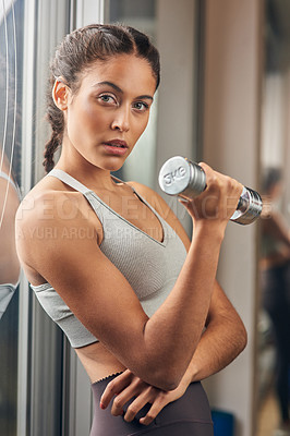 Buy stock photo Cropped portrait of an attractive young female athlete working out with a dumbbell in the gym