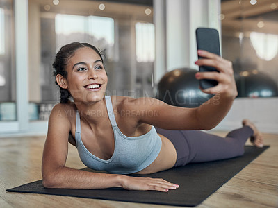 Buy stock photo Full length shot of an attractive young female athlete taking selfies in the gym