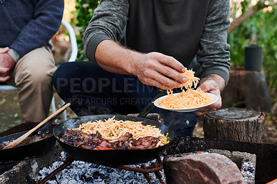 Buy stock photo Cropped shot of a man and his father having a barbecue in their backyard at home