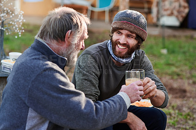 Buy stock photo Shot of a young man and his elderly father toasting with drinks while having a barbecue in their backyard