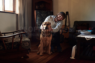 Buy stock photo Shot of a young man spending time with his adorable dog at home