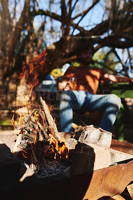 Buy stock photo Shot of an unrecognisable man relaxing by an open fire at a barbecue outdoors