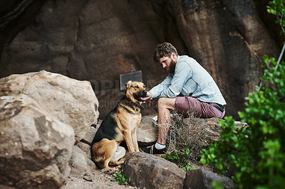 Buy stock photo Shot of a young man hiking in the mountains with his dog