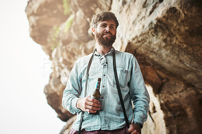 Buy stock photo Shot of a young man having a beer after taking a break from a hike up a mountain