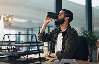 Buy stock photo Shot of a young businessman having coffee and using a computer during a late night in a modern office