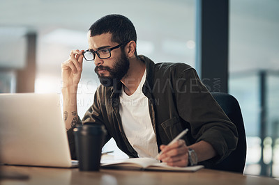 Buy stock photo Shot of a young businessman writing in a notebook and using a laptop during a late night in a modern office