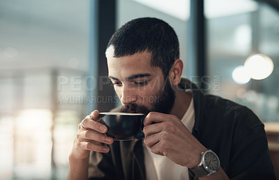 Buy stock photo Shot of a young businessman having a coffee break during a late night in a modern office
