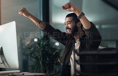 Buy stock photo Shot of a young businessman cheering while using a computer during a late night at work