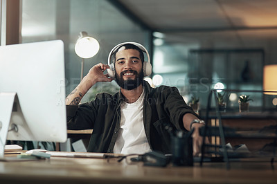 Buy stock photo Shot of a young businessman using a computer and headphones during a late night at work