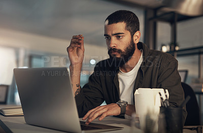 Buy stock photo Shot of a young businessman having takeout and using a laptop during a late night at work