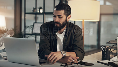 Buy stock photo Shot of a young man using a microphone and laptop during a late night at work