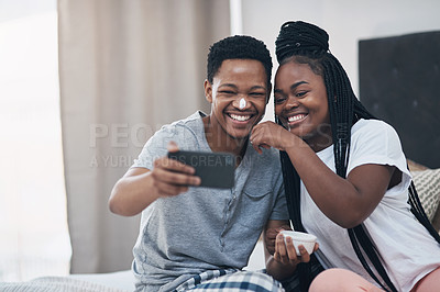 Buy stock photo Shot of a young couple taking selfies while getting homemade facials together at home