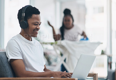 Buy stock photo Shot of a young man using a laptop while his wife irons clothing in the background