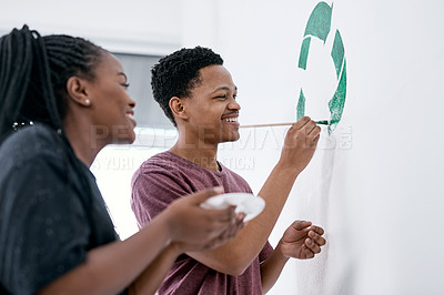 Buy stock photo Shot of a young couple painting a recycle symbol on a wall