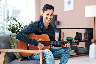 Buy stock photo Portrait of a young man playing a guitar at home