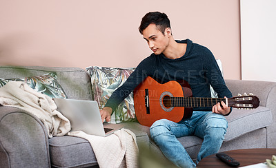 Buy stock photo Shot of a young man using a laptop while playing the guitar at home