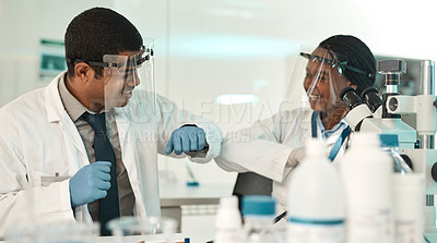 Buy stock photo Shot of two scientists bumping elbows while working together in a lab