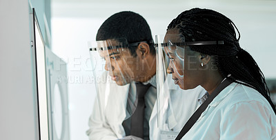 Buy stock photo Shot of two scientists wearing face shields while working together in a lab