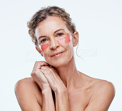 Buy stock photo Shot of a mature woman wearing under-eye gel patches while posing against a white background