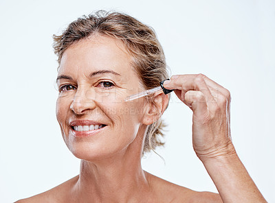 Buy stock photo Shot of a mature woman posing with a serum dropper against her face